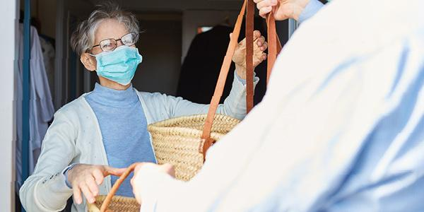 Volunteer giving an elderly women with a mask a basket of groceries